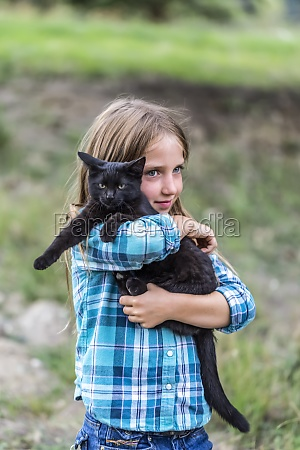 young girl with farm cat armstrong
