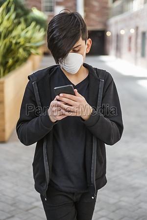 tween male using his smart phone
