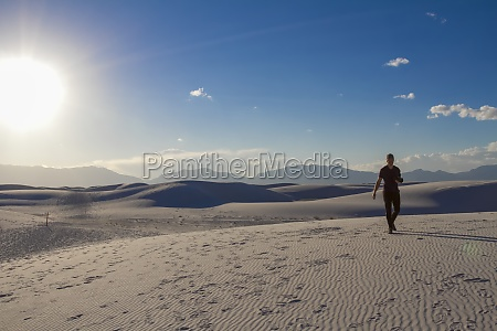 male photographer walks with camera on