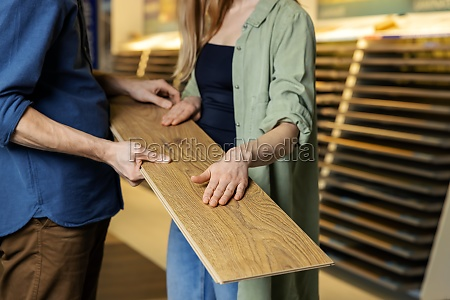 young couple choosing laminate floor design