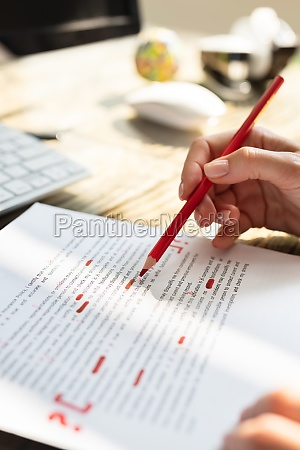 person marking error with red marker