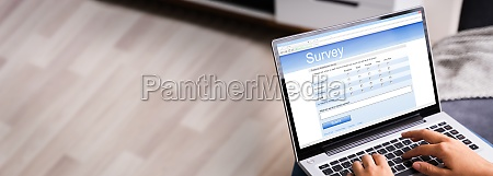 woman looking at online survey laptop