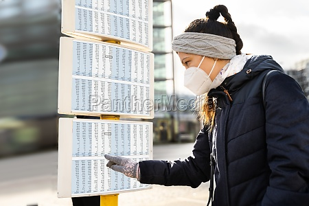 woman looking at bus stop timetable