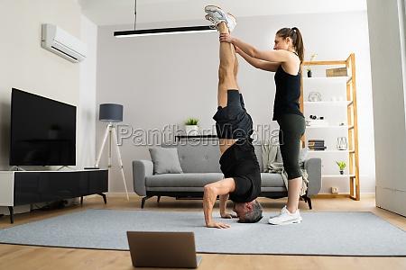 man doing yoga headstand exercise training