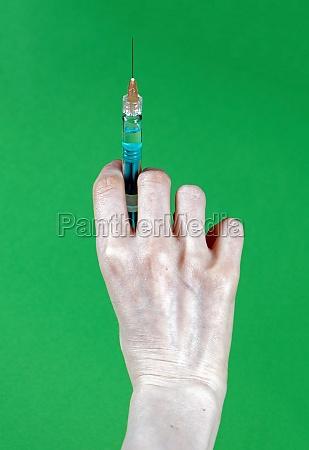 hand holding full syringe with needle
