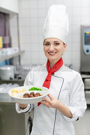 cook showing plate with food in