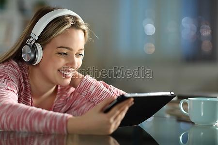 happy teen with headphones using tablet