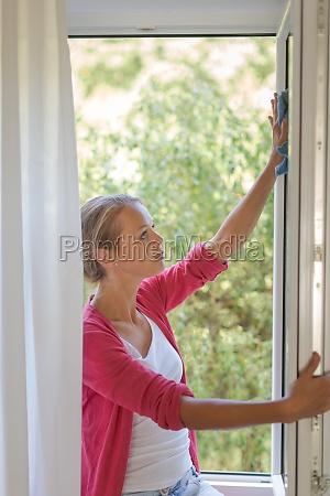 pretty young woman washing windows of