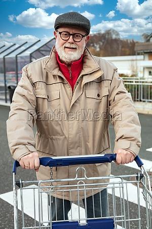 smiling senior pushing a shopping cart