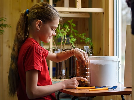 girl pouring soil into a plastic