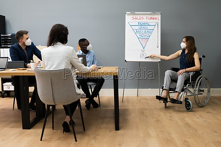 disabled person giving presentation to diverse