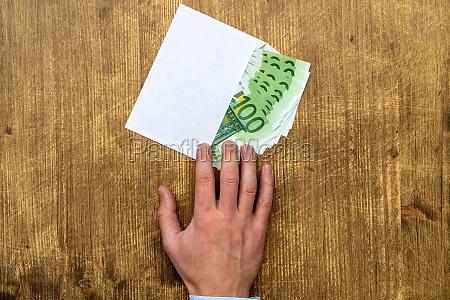 hand takes an envelope full of