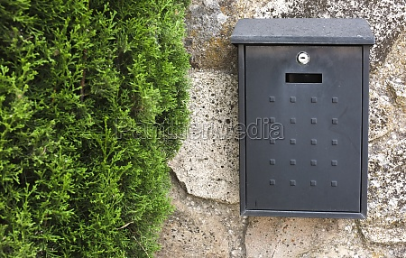 black metal mailbox attached on cottage