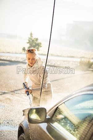 pretty young woman washing her car