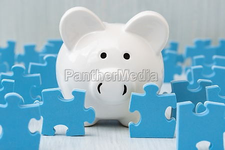 piggy bank surrounded by puzzle pieces