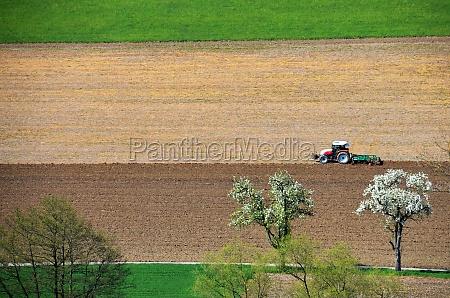 traktor beim eggen im salzkammergut OEsterreich