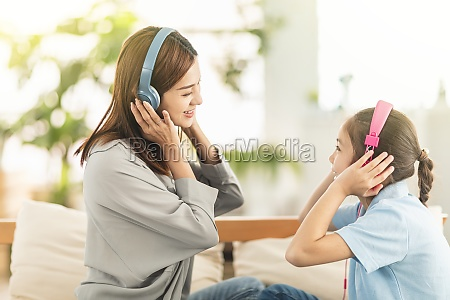 happy daughter and mother listening music