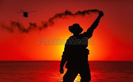 soldier signaling for helicopter with smoke