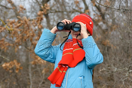 girl enthusiastically looks through binoculars front