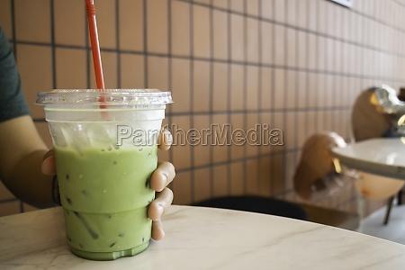 hand on iced matcha green tea