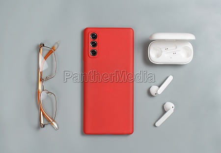 smartphone glasses and white wireless earphones