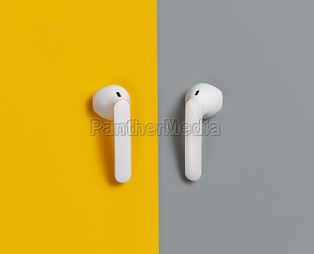 white wireless earphones on yellow and