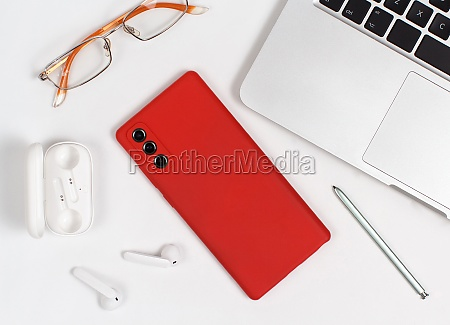 red mobile phone earphones and glasses