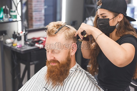 woman barber making haircut to redhaired