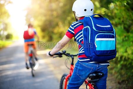 children with rucksacks riding on bikes