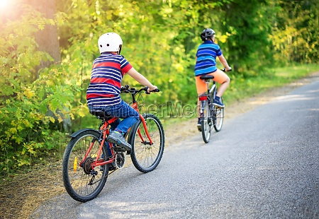 two boys riding on bicycles on