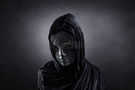 scary figure with hooded cape in