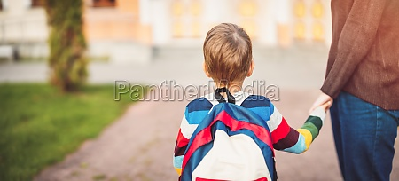 child with rucksack and with mother
