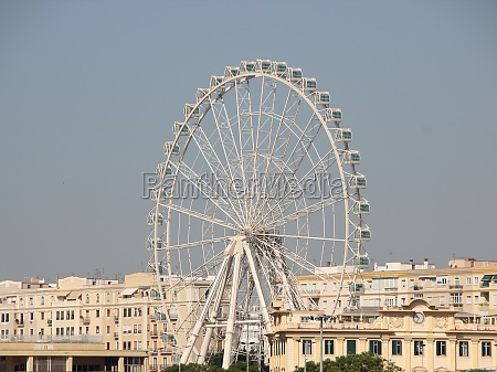 large white ferris wheel with city