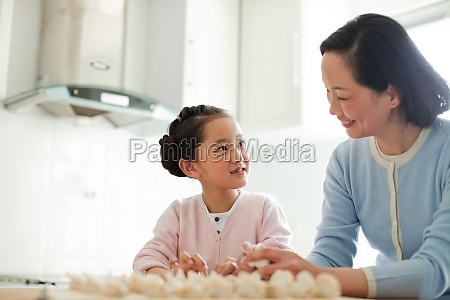 adult elder making dumplings granddaughter traditional