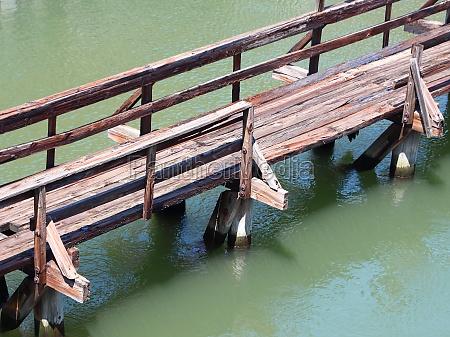 wooden bridge over green water aerial