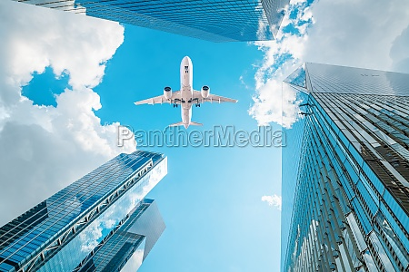 an airplane flies over skyscrapers