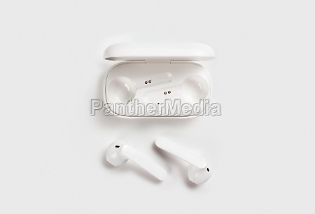 white wireless earphones with case on