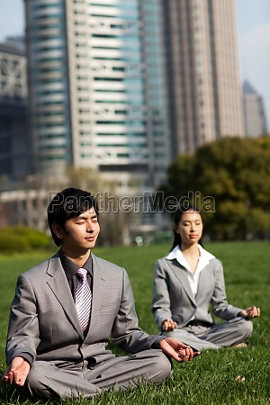 business people practicing yoga outdoors