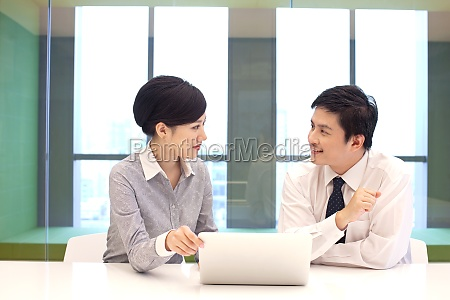 office discussion oriental figures two people