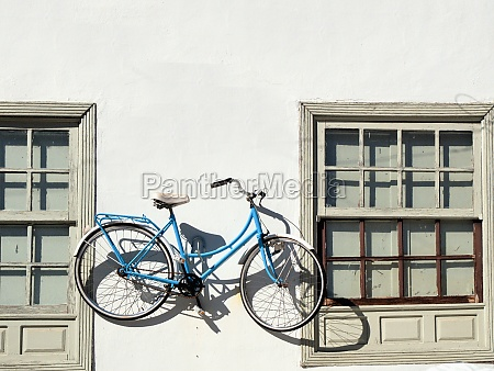 a white and blue bicycle hangs