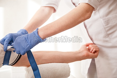 nurse fastens the medical tourniquet on