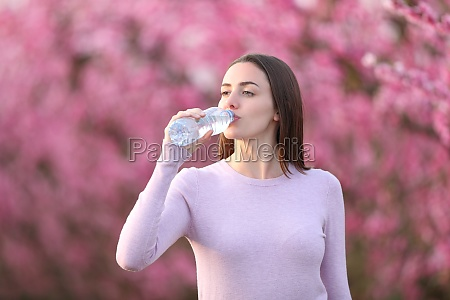 woman drinking water from bottle in