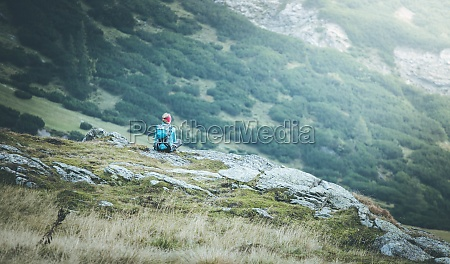 mountain climber with backpack is sitting