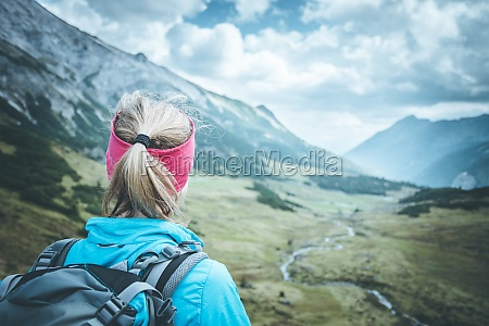 female blonde mountain climber with backpack