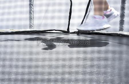 little girl feet jumping on trampoline