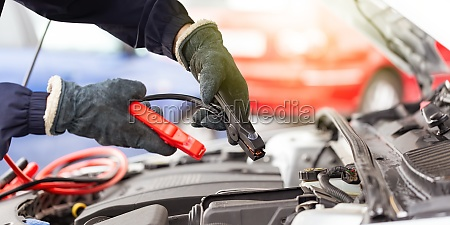human hands with jumper cable over