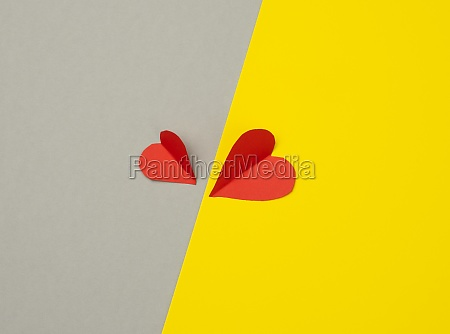 two paper hearts on a yellow