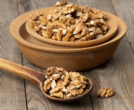 peeled walnuts in a wooden plate