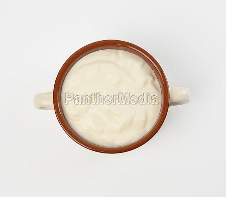 sour cream in a brown ceramic