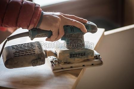 sanding wood plank using electric sand